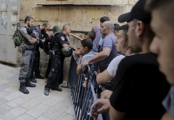 Palestinians confronts Israeli police officers at a gate of Aqsa Mosque in Jerusalem's Old City September 15, 2015. Reuters