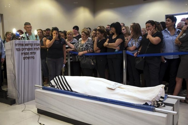Friends and relatives mourn next to the body of Alexander Levlovich during his funeral in Jerusalem September 16, 2015. REUTERS