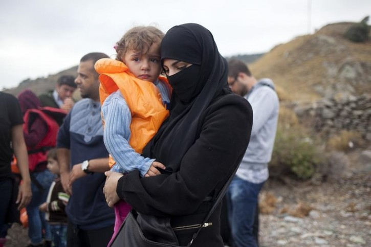 FILE- A Syrian refugee holds a child following their arrival on the Greek island of Lesbos after crossing a part of the Aegean Sea from the Turkish coast, September 29, 2015. Reuters