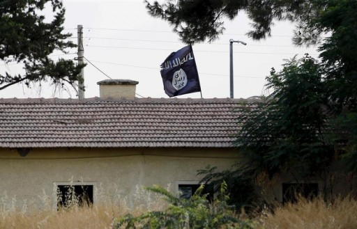 FILE - An Islamic State flag flies over the custom office of Syria's Jarablus border gate as it is pictured from the Turkish town of Karkamis, in Gaziantep province, Turkey August 1, 2015.REUTERS