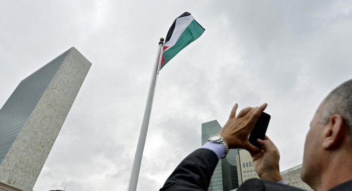 A man takes a picture of the Palestinian flag flying over United Nations headquarters in New York, New York, USA, 30 September 2015. EPA