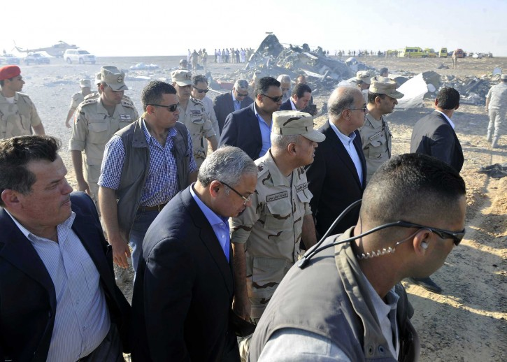In this image released by the Prime Minister's office, Sherif Ismail, third right, along with milirary and government officials, tour the site where a passenger plane crashed in Hassana Egypt, Friday, Oct. 31, 2015. AP