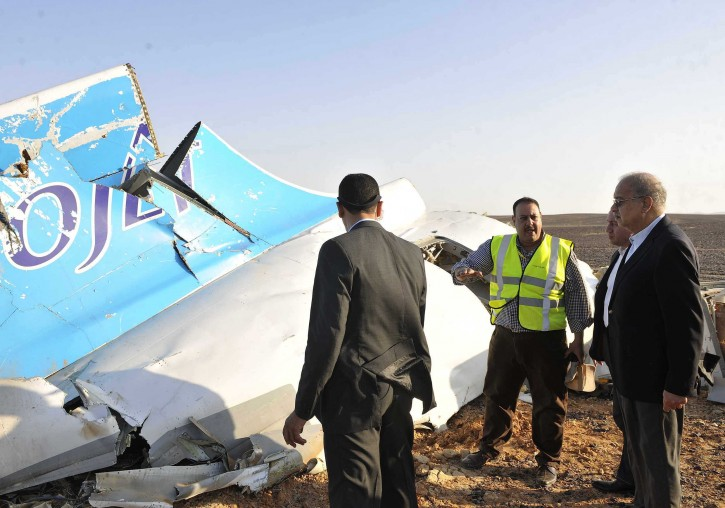 In this image released by the Prime Minister's office, Sherif Ismail, right, looks at the remains of a crashed passenger jet in Hassana Egypt, Friday, Oct. 31, 2015.  AP