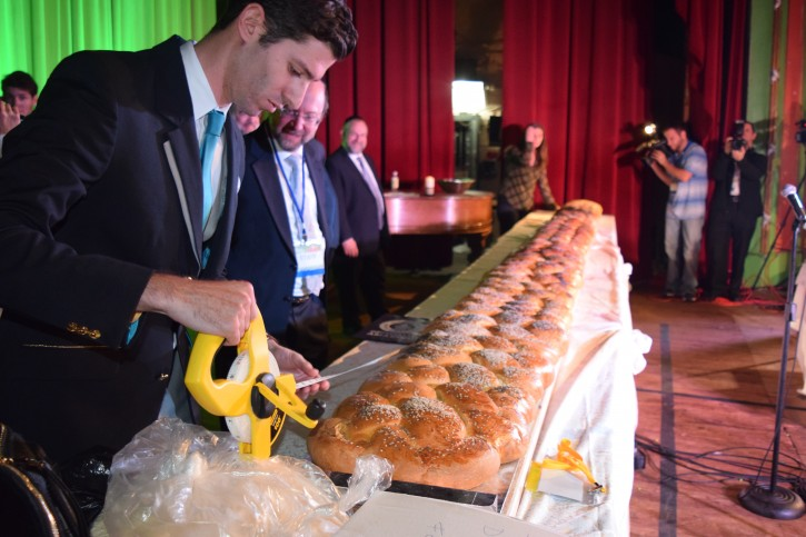 Alex Angert of Guinness measures the Challah in the Grand Prospect Hall in Park Slope, Brooklyn on Oct. 21, 2015. (sandy Eller/VINnews.com)