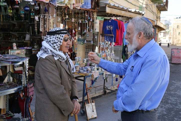 A Palestinian and a Jew seen talking outside a shop near the Cave of the Patriarchs in Hebron, on December 10, 2014. Photo by Gershon Elinson/Flash90