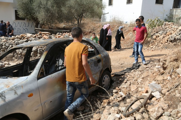 A Palestinian boy looks at a car belonging to Palestinians, which residents said was burnt by alleged Jewish settlers, in Beit Ilu village near the West Bank city of Ramallah on October 2, 2015. An Israeli couple was murdered last night while driving through the West Bank, an Israeli forces were searching the area for the suspected Palestinian attackers, authorities said. Photo by Flash90