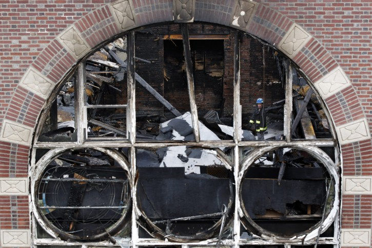 An investigator looks through the rubble in the burned shell of the Poile Zedek Synagogue on  Saturday, Oct. 24, 2015, in New Brunswick, N.J.  Authorities say a fire that destroyed the historic New Jersey synagogue on Friday appears to be accidental. (AP Photo/Mel Evans)