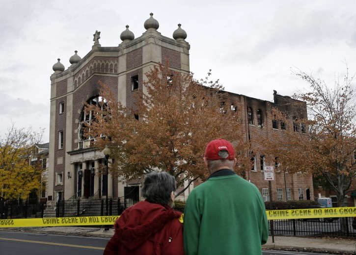 A couple stops to look at the burned shell of the Poile Zedek Synagogue from a fire Friday, on Saturday, Oct. 24, 2015, in New Brunswick, N.J.  Authorities say a fire that destroyed the historic New Jersey synagogue appears to be accidental. (AP Photo/Mel Evans)