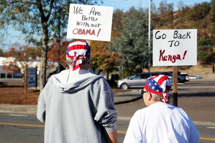 Demonstrators wait outside of Roseburg Regional Airport for President Barack Obama's arrival, Friday, Oct. 9, 2015, in Roseburg, Ore. Angry with Obama for calling for tighter gun restrictions in the wake of last week's deadly shootings at Umpqua Community College, gun-rights activists gathered to protest the president's visit to meet with victims' families. (AP Photo/Ryan Kang)