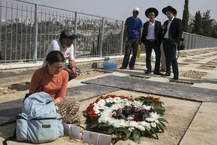 Mourners stand beside the fresh grave of Eitam and Na'ama Henkin after their funeral at a cemetery in Jerusalem October 2, 2015. Reuters