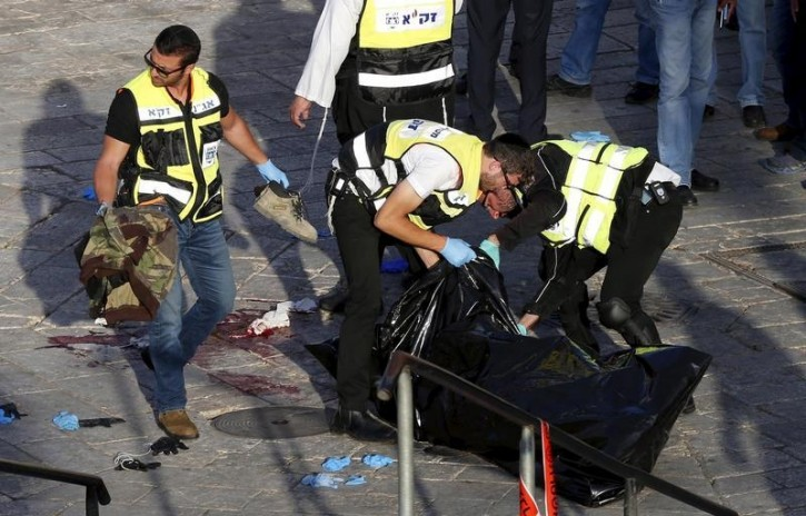 Members of Zaka Rescue and Recovery team check the  body of a Palestinian man, who attempted to stab paramilitary police and was shot dead according to an Israeli police spokeswoman, at an entrance to Jerusalem's walled Old City October 14, 2015. Reuters