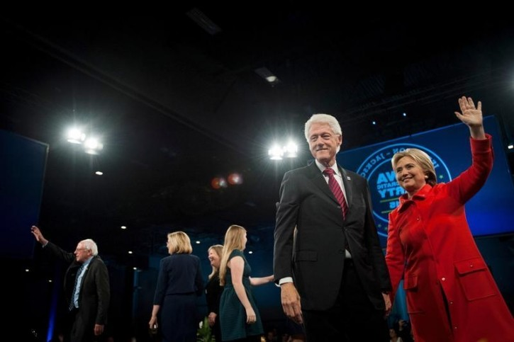 Former U.S. President Bill Clinton (2nd R) and Democratic presidential candidate Hillary Clinton (R) greet the crowd as Democratic presidential candidate Bernie Sanders (L) waves at the end of the Jefferson-Jackson Dinner in Des Moines, Iowa October 24, 2015. REUTERS/Mark Kauzlarich -