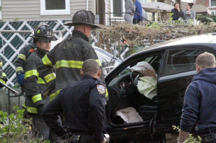 First responders examine an automobile after its driver lost control and plowed into a group of trick-or-treaters in New York, Saturday, Oct. 31, 2015. Three people were killed in the mishap, including a 10-year-old girl. Four others were injured. (AP Photo/David Greene)