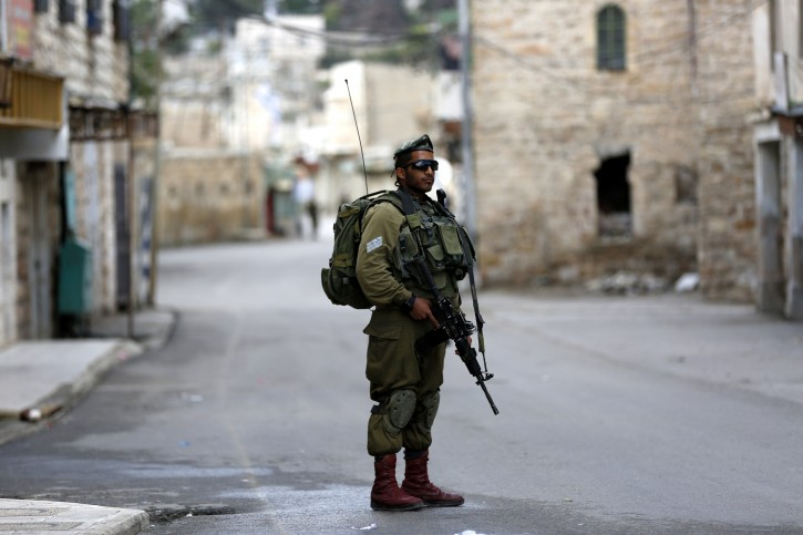 An Israeli border guard soldier patrols close to a checkpoint near the Ibrahimi mosque in the flashpoint West Bank city of Hebron, 30 October 2015.