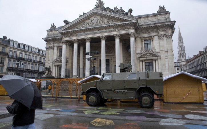 A man walks by a military vehicle in front of the old stock exchange in the center of Brussels on Saturday, Nov. 21, 2015. Belgium raised its security level to its highest degree on Saturday as the manhunt continues for extremist Salah Abdeslam who took part in the Paris attacks. The security levels shut down all metro lines and shuttered many shops as well as canceling sports matches. (AP Photo/Virginia Mayo)