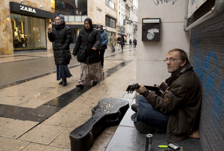 Two women walk by a street musician on an otherwise busy shopping street in Brussels on Saturday, Nov. 21, 2015. Belgium raised its security level to its highest degree on Saturday as the manhunt continues for extremist Salah Abdeslam who took part in the Paris attacks. The security levels shut down all metro lines and shuttered many shops as well as canceling sports matches. (AP Photo/Virginia Mayo)