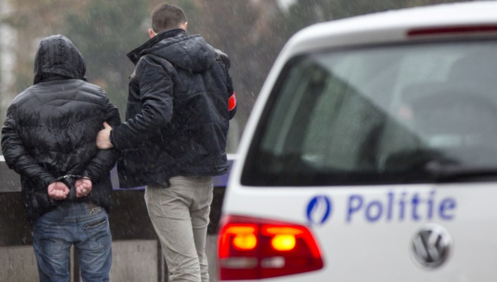 Police detain a man in handcuffs, left, after stopping and searching his car which had French number plates in Brussels on Saturday, Nov. 21, 2015. Belgium raised its security level to the highest degree on Saturday as the manhunt continues for extremist Salah Abdeslam who took part in the Paris attacks. The security alert shut metros, shops, and cancelled events with high concentrations of people. (AP Photo/Virginia Mayo)