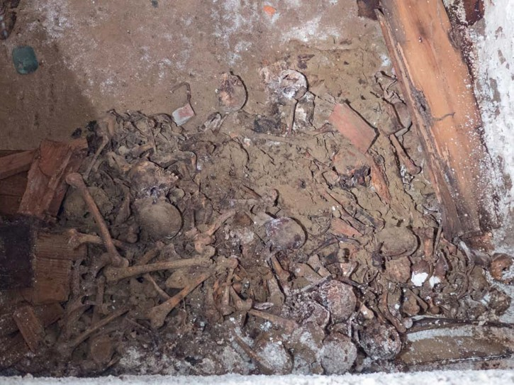 This Nov. 3, 2015 photo provided by the New York City Department of Design and Construction shows human remains in a centuries-old burial vault beneath a street in New York's Greenwich Village neighborhood according to anthropologists and archeologists. Two vaults were discovered by workers replacing a water main in the heart of New York University's campus. One of the roughly 15-by-18-foot crypts contained skeletons and skulls of between 9 and 12 people pushed into a corner while more than a dozen stacked wooden coffins can be seen in the second one.  (New York City Department of Design and Construction via AP)