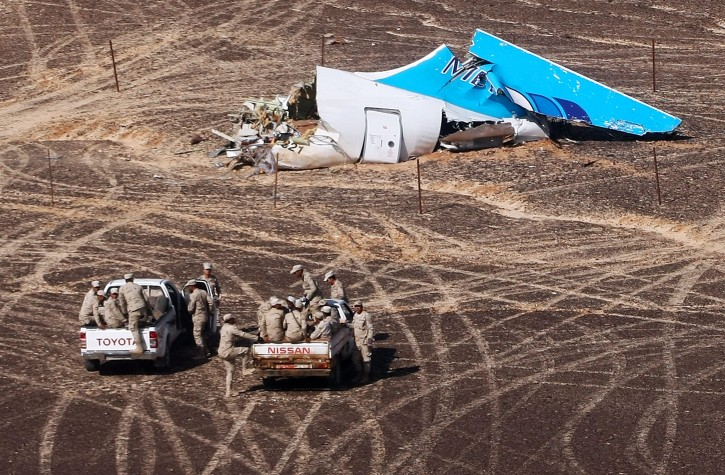 In this photo made available Monday, Nov. 2, 2015, and provided by Russian Emergency Situations Ministry, Egyptian Military on cars approach a plane's tail at the wreckage of a passenger jet bound for St. Petersburg in Russia that crashed in Hassana, Egypt, on Sunday, Nov. 1, 2015. (Maxim Grigoriev/Russian Ministry for Emergency Situations via AP)
