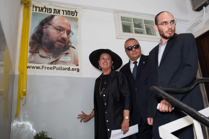 FILE - Esther Pollard, wife of convicted Israeli spy Jonathan Pollard, walks past a poster of her husband prior to speaking to press outside her home in Jerusalem on July 29, 2015.  Flash90