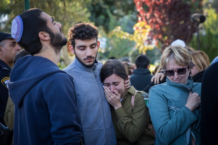 Friends and family seen mourning over the grave of Ziv Mizrahi during the funeral ceremony of the 18-year-old soldier at Mount Herzl Military Cemetery in Jerusalem, on November 24, 2015. Mizrahi was murdered in a stabbing attack at a gas station on the 443 Road, near Jerusalem. Photo by Hadas Parush/Flash90