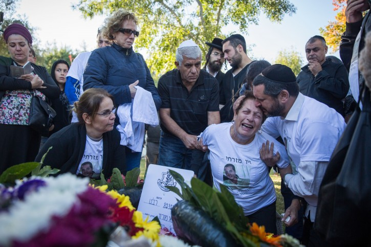 Friends and family seen mourning over the grave of Ziv Mizrahi during the funeral ceremony of the 18-year-old soldier at Mount Herzl Military Cemetery in Jerusalem, on November 24, 2015. Mizrahi was murdered in a stabbing attack at a gas station on the 443 Road, near Jerusalem. Photo by Hadas Parush/Flash9*0
