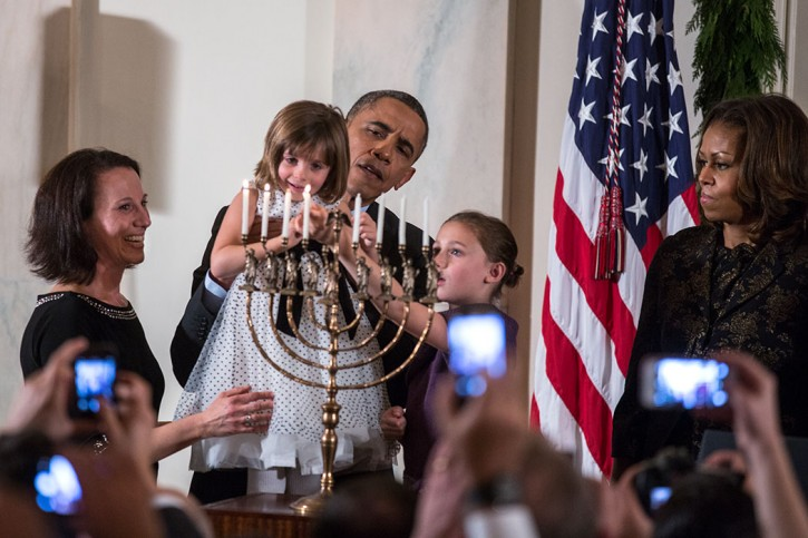FILE - President Barack Obama holds up Kylie Schmitter as she and her sister Lainey Schmitter light the menorah during the Hanukkah reception #1 in the Grand Foyer of the White House, Dec. 5, 2013. (Official White House Photo by Lawrence Jackson)