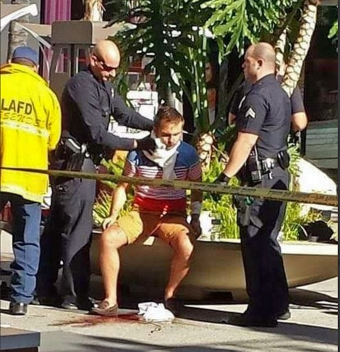 In this photo provided by Liza Brown, authorities care for a man after he was stabbed on the Hollywood Walk of Fame in Los Angeles, Wednesday, Nov. 18, 2015. Police say the tourist was attacked across from the TLC Chinese Theatre. (Liza Brown via AP)