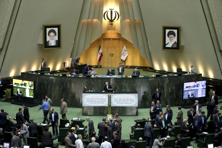 FILE - In this  Sunday, Oct. 11, 2015 file photo, the head of Iran's Atomic Energy Organization Ali Akbar Salehi, center, ends his speech in an open session of parliament while discussing a bill on Iran's nuclear deal with world powers, in Tehran, Iran. (AP Photo/Ebrahim Noroozi, File)