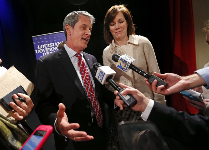 FILE - In this Monday, Nov. 16, 2015, file photo, Louisiana gubernatorial candidate Sen. David Vitter, R-La., left, speaks to reporters after his debate against Democratic candidate John Bel Edwards, in Baton Rouge, La.Vitter's wife Wendy, right, looks on. Louisiana voters are deciding on Saturday, Nov. 21 whether to elect a Democrat to statewide office for the first time since 2008. (AP Photo/Gerald Herbert)