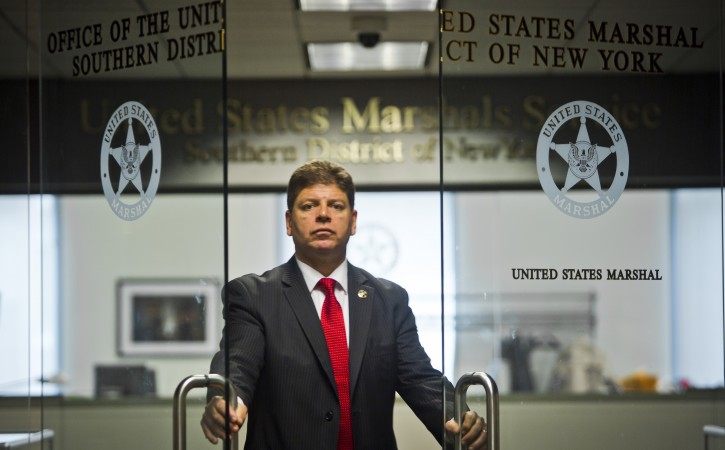 U.S. Marshall Director Michael Greco pose at the entrance to his office, Thursday, Oct. 8, 2015, in New York.  Greco was recently named the first Hispanic U.S. marshal in the judicial district that includes Manhattan.(AP Photo/Bebeto Matthews)