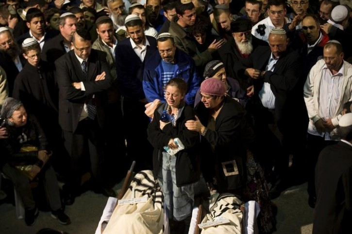 A member of the family (C) mourns next to the bodies of Yaakov Litman and his son Natanel during their funeral in Jerusalem November 14, 2015. Reuters