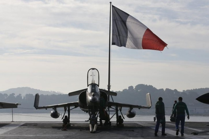 Flight deck crew work around a Super Etendard fighter jet as a French flag flies aboard the French nuclear-powered aircraft carrier Charles de Gaulle before its departure from the naval base of Toulon, France, November 18, 2015. Reuters