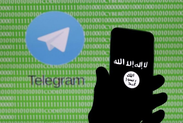 FILE - A man holds a smartphone showing the Islamic State logo. Reuters