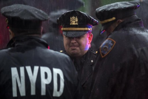 FILE - Police officers stand in the rain near the Greater Allen A.M.E. Cathedral of New York during the funeral service for slain New York City Police (NYPD) officer Randolph Holder in the Queens borough of New York City, October 28, 2015. REUTERS