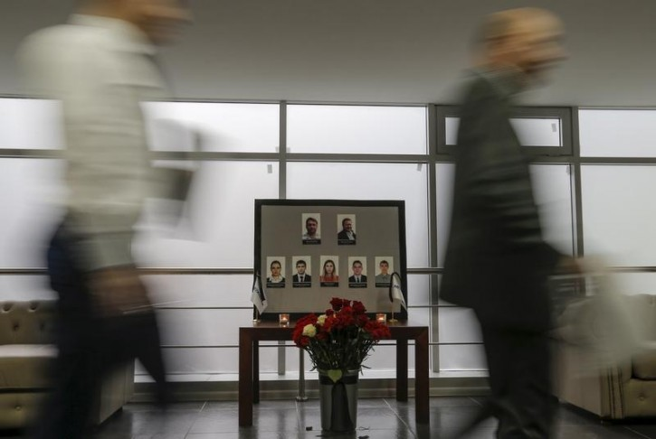 People walk past portraits of the crew members of the crashed Airbus A321 plane, operated by Russian airline Kogalymavia, in the company's office in Moscow, Russia November 2, 2015.  Reuters