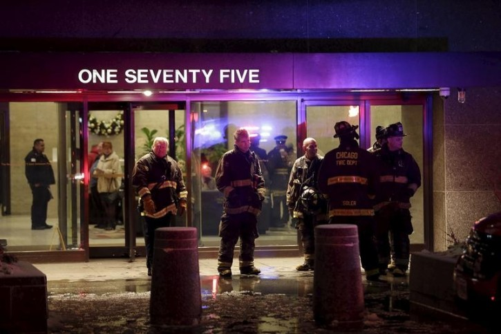 Firefighters stand near the entrance of the John Hancock Center after extinguishing a 2-11 alarm fire on the 50th floor in Chicago, Illinois November 21, 2015. Five people were injured, none seriously, on Saturday in a fire that sent flames bursting out of windows from a residence on the 50th floor of the Chicago's famous John Hancock Center, according to the Chicago Fire Department. The fire broke out on the east side of the 100-story building in mid-afternoon and was quickly extinguished by responding firefighters, according to tweets by the Chicago Fire Department. REUTERS/Joshua Lott