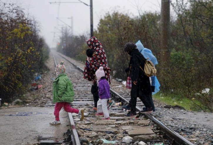 FILE - A Syrian refugee family walks over rail tracks into Macedonia after crossing the border from Greece during a rain storm near the Macedonian town of Gevgelija November 27, 2015.REUTERS