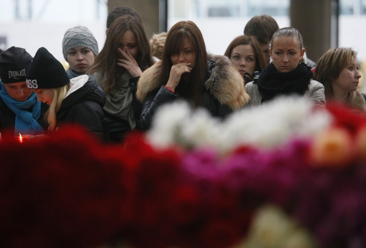 People react as they come to lay flowers and toys at an entrance of Pulkovo airport outside St. Petersburg, Russia, during a day of national mourning for the plane crash victims, on Sunday, Nov. 1, 2015. Hundreds of people are bringing flowers and pictures to St. Petersburg's airport to commemorate the 224 victims of Saturday's Russian plane crash in Egypt. (AP Photo/Dmitry Lovetsky)