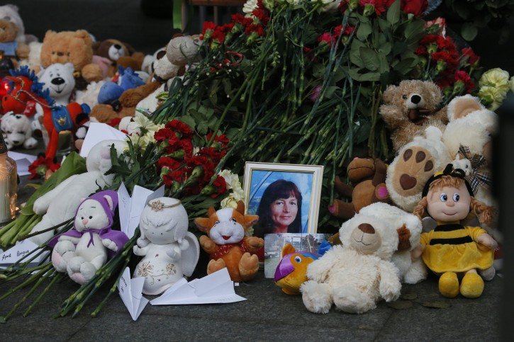 A portrait of one of victims lies next to the toys and flowers at an entrance of Pulkovo airport outside St.Petersburg, Russia, during a day of national mourning for the plane crash victims, on Sunday, Nov. 1, 2015. Hundreds of people are bringing flowers and pictures to St. Petersburg's airport to commemorate the 224 victims of the Russian plane crash in Egypt. (AP Photo/Dmitry Lovetsky)