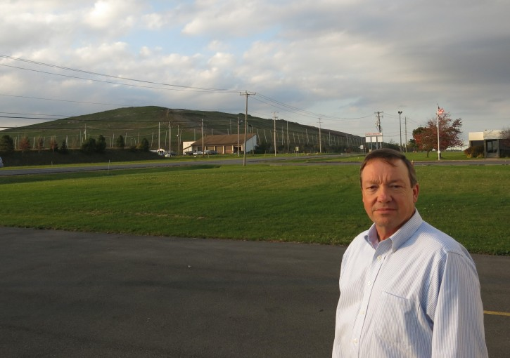 In this photo taken on Oct. 22, 2015, Rich Swinehart, CEO of Waterloo Container, which provides bottles to wineries in the Finger Lakes region, stands outside his business with the Seneca Meadows Landfill in the background. Swinehart and a coalition of winemakers and other business people and local residents want the landfill shut down, saying it's bad for tourism in the Finger Lakes wine country. Swinehart says a new 20-year contract to ship New York City trash to the landfill by train will only extend the life of the facility. (AP Photo/Mary Esch)