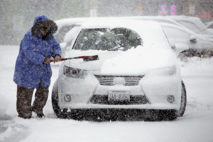 A woman cleans snow from her car on Saturday, Nov. 21, 2015, in Northbrook, Ill. The first significant snowstorm of the season blanketed some parts of the Midwest with more than a foot of snow and more was on the way Saturday, creating hazardous travel conditions and flight delays. (AP Photo/Nam Y. Huh)