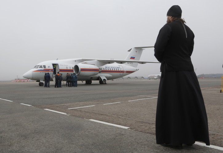 An Orthodox priest looks on as a Russian Ministry for Emergency Situations plane carrying bodies of victims of the Russian plane crash in Egypt, at Pulkovo airport outside St. Petersburg, Russia, 06 November 2015.  Reuters