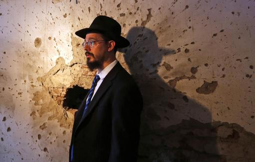 FILE - Rabbi Moshe Gourarie from New Jersey looks at a room riddled with bullet marks from the 2008 terror attack at the Chabad Center, during the reopening of the Jewish center in Mumbai, India, Tuesday, Aug. 26, 2014.  (AP Photo/Rajanish Kakade)