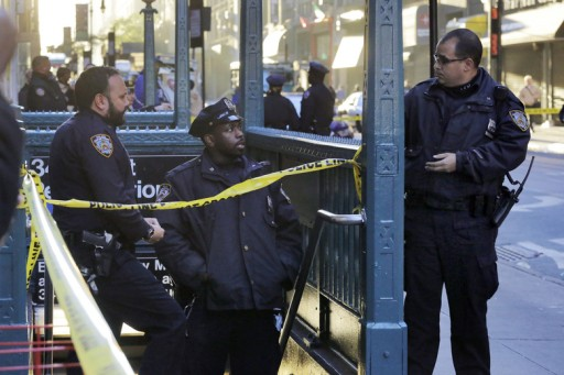 FILE - New York Police Department officers seen at a subway station entrance in Manhattan, Monday, Nov. 9, 2015, in New York. (AP Photo/Mark Lennihan)