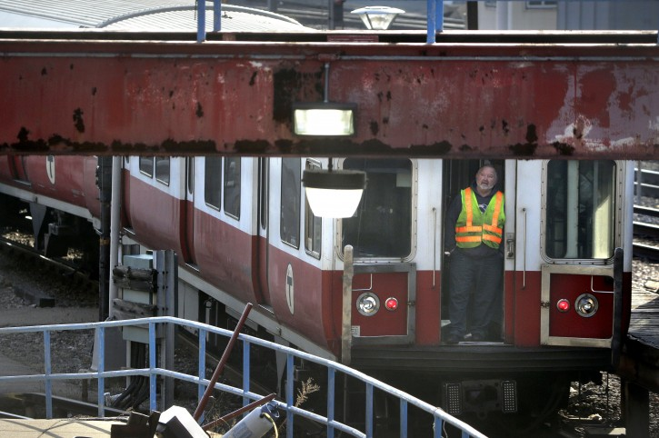 A worker stands at an entrance to a passenger train as it rests on tracks Thursday, Dec. 10, 2015, in Boston. The six-car train with passengers on board left a suburban Boston transit station without a driver Thursday and went through four stations without stopping, was tampered with, Massachusetts Gov. Charlie Baker said. (AP Photo/Steven Senne)