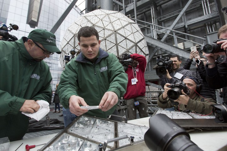 Electricians Nick Bonavita, left, and Jason Andrle install triangular crystals into a panel they are installing on the Waterford crystal ball, background, on the roof of One Times Square, Sunday, Dec. 27, 2015, in New York. Hundreds of thousands of people in Times Square are expected to watch the ball drop at midnight Thursday. (AP Photo/Mark Lennihan)