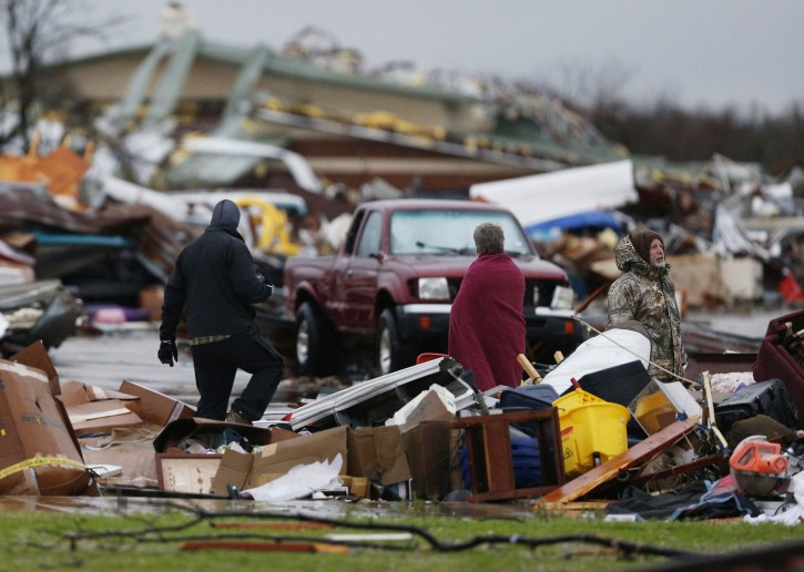 People assess the damage to a storage facility destroyed by Saturday's tornado in Garland, Texas, Sunday, Dec. 27, 2015. Tornadoes that swept through the Dallas area caused substantial damage and at least 11 people died either from the storm or related traffic accidents and dozens of people were injured. (Nathan Hunsinger/The Dallas Morning News via AP)