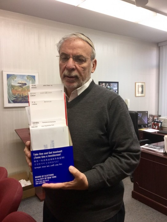 Assemblyman Dov Hikind is pictured with voter registration forms that were mailed to his office in various languages, except one—Yiddish.