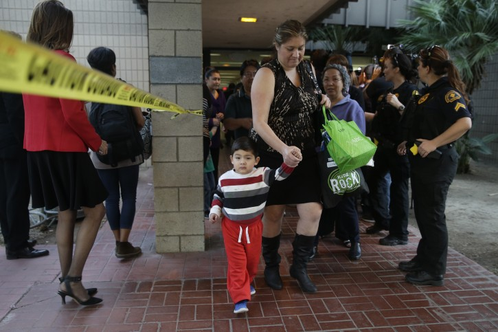 People who were near a shooting rampage that killed multiple people at a social services center, Wednesday, Dec. 2, 2015, leave a community center after they reunited with friends and family in San Bernardino, Calif. (AP Photo/Jae C. Hong)